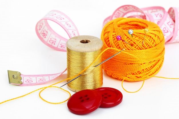 Colored threads with needles for embroidery, on a white background