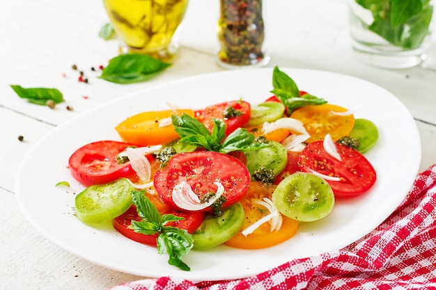 Colored tomato salad with onion and basil pesto.