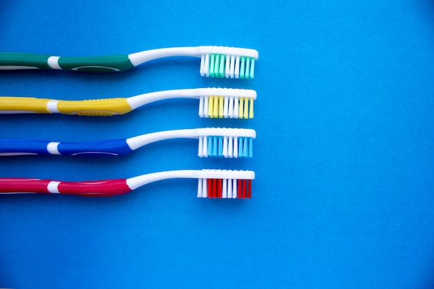 Colored toothbrushes on a blue