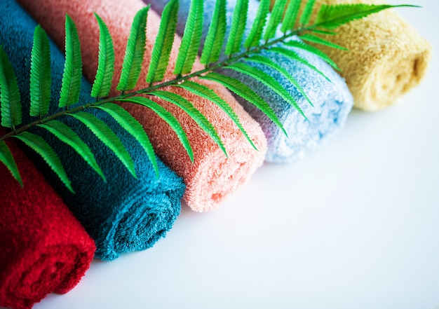 Colored towels and fern leaves on white table with copy space on bath room background.