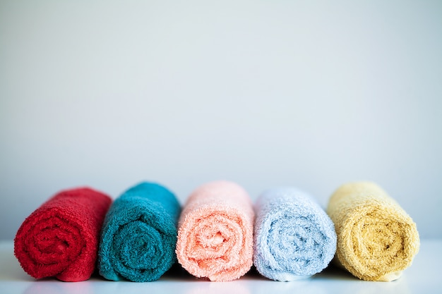 Colored towels on white table with copy space on bathroom.