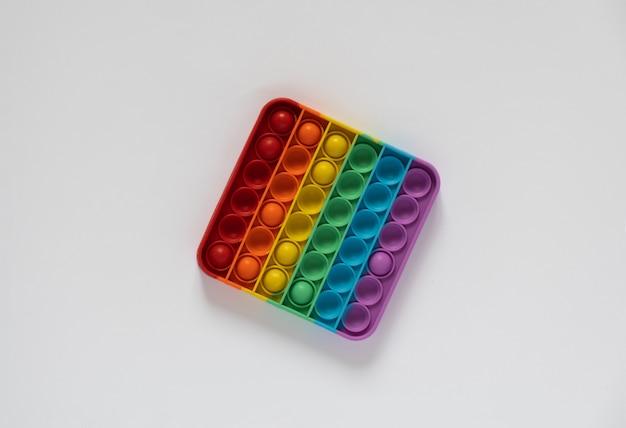 子供のための着色されたおもちゃの抗ストレスはそれをポップします。白い背景で隔離の虹色の正方形。