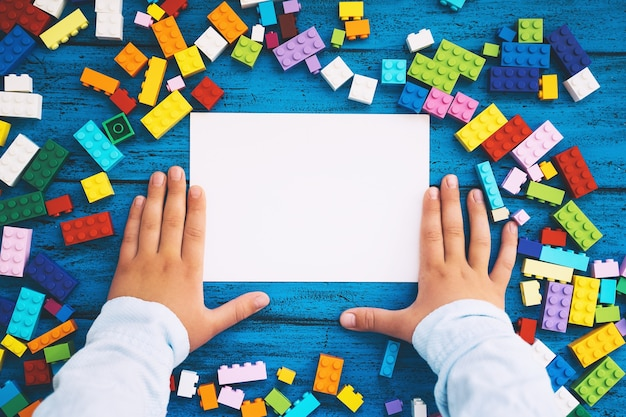 Colored toy bricks and blank card with child handskids leisure and education at home or class