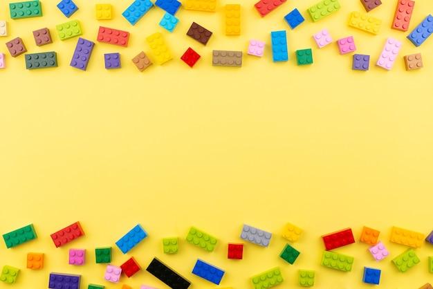 テキスト用のスペースがある色付きのおもちゃのレンガ。おもちゃの黄色の背景。