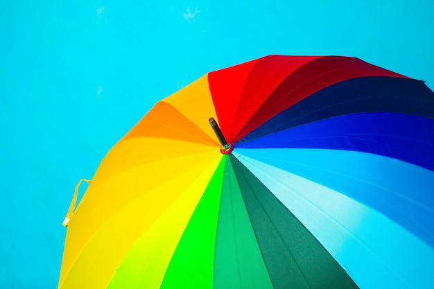 青い背景の色の傘。明るい傘。スペースをコピーします。雨からの保護に関する記事。
