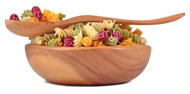Colored uncooked italian pasta fusilli in a wooden bowl on a white background