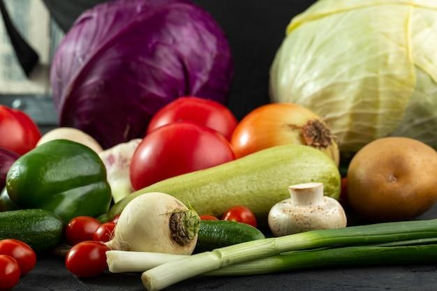 Verdure di insalata fresche fresche delle verdure colorate come midollo verde ed altre sullo scrittorio grigio