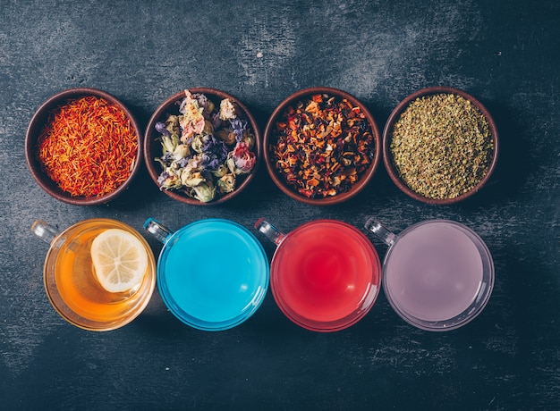 Colored water in a cups with with tea herbs in bowls flat lay on a dark textured background
