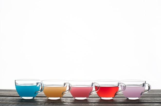 Покрашенная вода в чашках на белой предпосылке. вид сбоку. место для текста