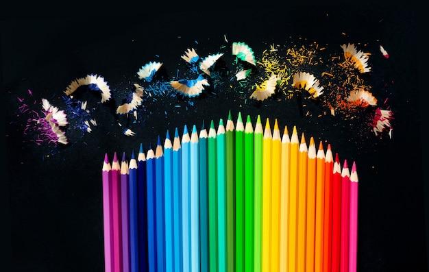 Цветные акварельные карандаши на черном фоне. заточка карандашей. горизонтальное изображение
