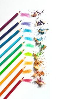 Цветные акварельные карандаши на белом фоне. заточка радужных карандашей. вертикальное изображение