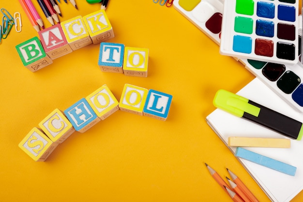 Colored wooden alphabetical cubes on bright yellow background
