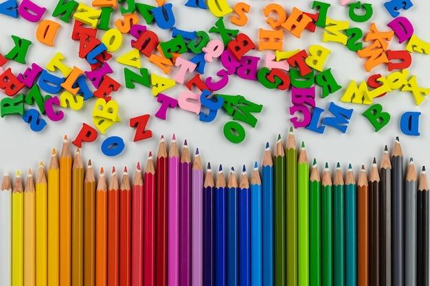 Цветные деревянные карандаши и буквы английского алфавита на белом фоне, копией пространства