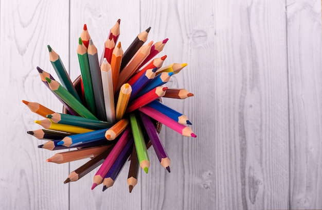 Colored wooden pencils, in a brown leather beaker, seen from above,