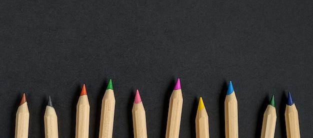 검은 종이 바탕에 색된 나무 연필입니다. 학용품