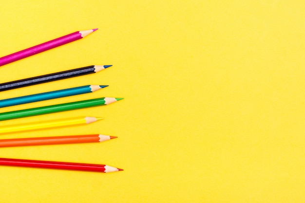 Colored wooden pencils on a yellow background