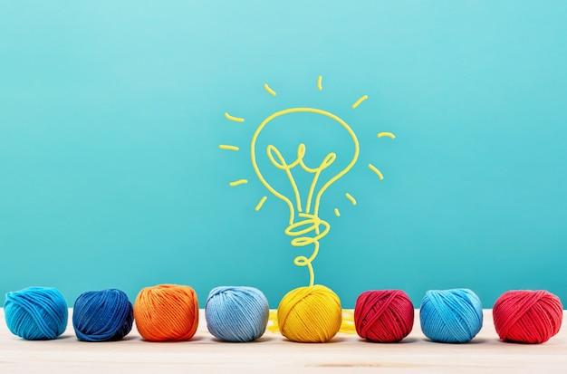ワイヤーで電球を作る色のウールボール。創造性とアイデアの概念