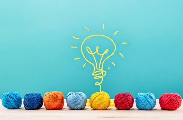 Colored wool balls that do a lightbulb with the wire. concept of creativity and idea