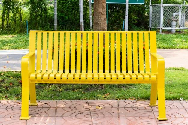 Цветная желтая скамейка в парке на открытом воздухе