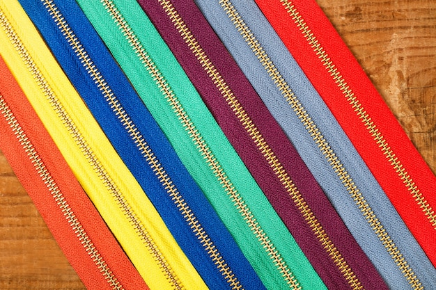 Colored zippers on a wooden table in a top view