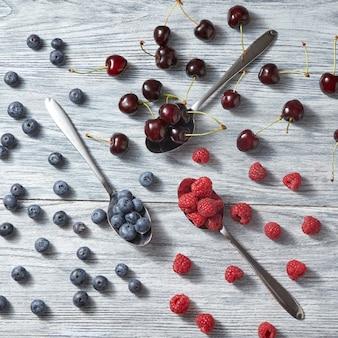 회색 나무 배경에 다양 한 열매와 세 숟가락의 다채로운 패턴입니다. 건강한 유기농 식사의 개념