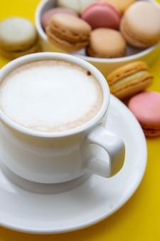 Чашка кофе и миндальное печенье на colorfu lyellow таблице.