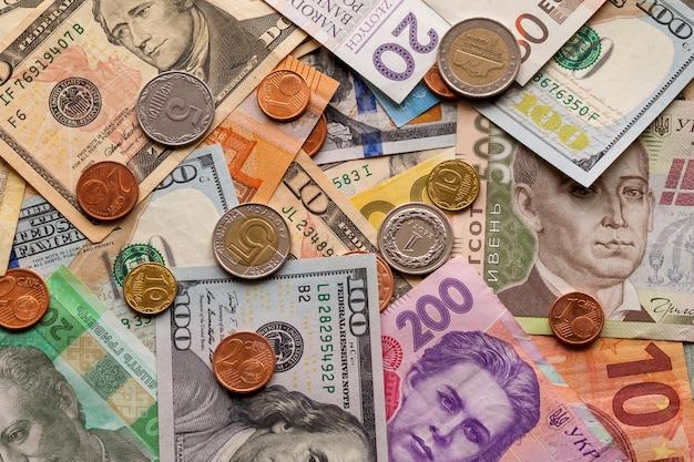 Красочная абстрактная предпосылка сделанная различных монеток металла, счетов американца, украинца и валюты банкнот евро. деньги и финансы, успешная инвестиционная концепция.