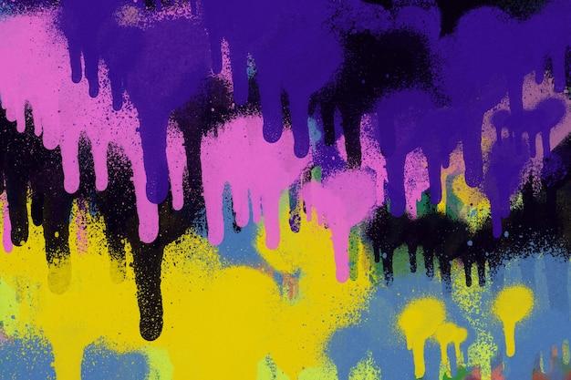 カラフルな抽象的なペンキが落書きの壁の背景を漏らします