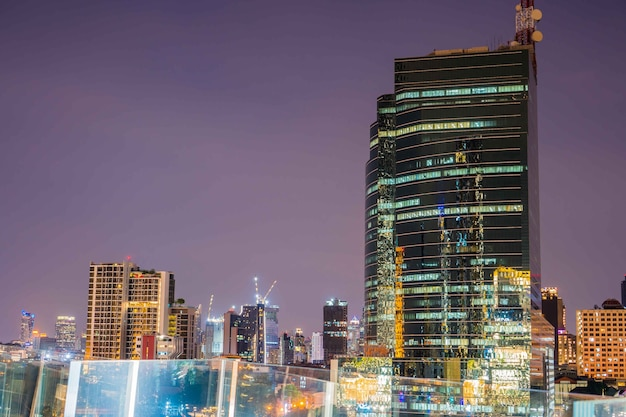 도시의 현대적인 건물이 흐릿한 화려한 추상 사진은 황혼의 시간에 방콕의 도시 경관을 흐리게 하며, 태국 방콕에 있는 건물을 반영하는 디포커스 보케 도시 사무실로 장식되어 있습니다.