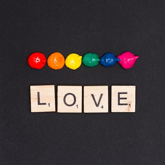Colorful acrylic drops and sign love on black background