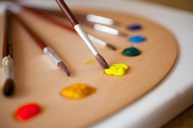 木製パレットにカラフルなアクリル絵の具。黄色いペンキに浸した絵筆に焦点を当てる
