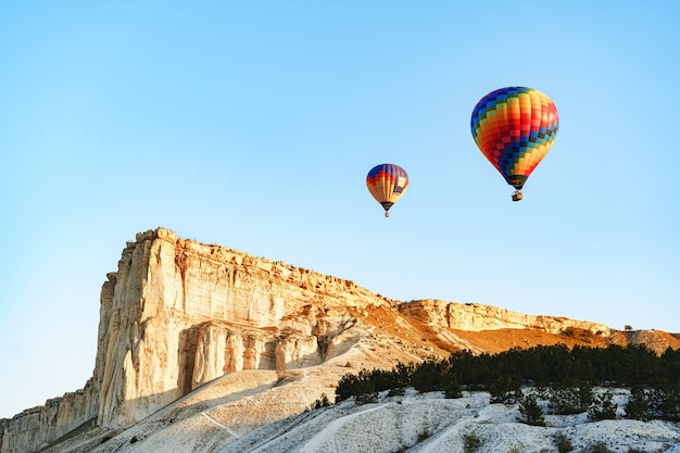 Colorful air balloons flying in clear sky near huge white mountain on sunny day