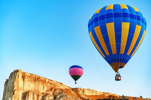 Colorful air balloons flying in clear sky near huge white mountain