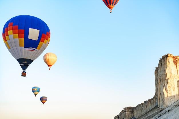 화창한 날에 거대한 하얀 산 근처 맑은 하늘에서 날아 다니는 다채로운 공기 풍선
