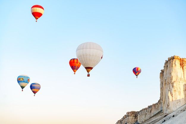 巨大な白い山の近くの澄んだ空を飛んでいるカラフルな気球
