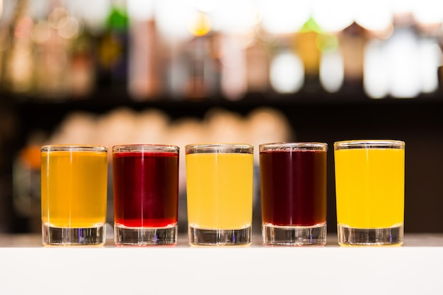 Colorful alcohol shots on a blurry bokeh background