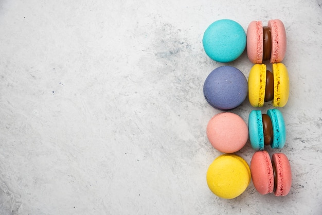 Colorful almond macarons on white background. top view.