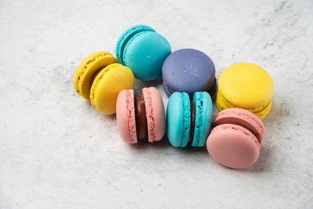 Colorful almond macarons on white surface. close up.