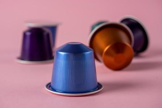 紙のバラの背景に挽いたコーヒーとカラフルなアルミニウムカプセル。コーヒーマシン用カプセル