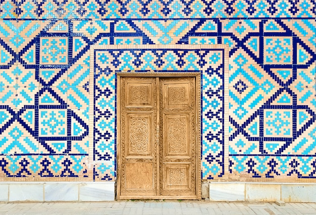 Colorful ancient traditional uzbek pattern on the ceramic tile on the wall of the mosque, abstract background