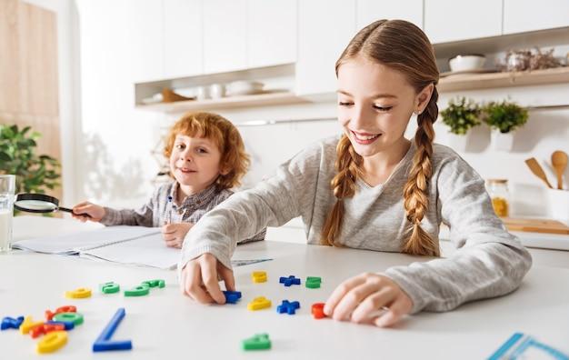 カラフルで簡単。彼女の兄弟に数学を説明するいくつかのプラスチックの数字を使用しながら、太陽に照らされた部屋の白いテーブルに座っている美しい活気のあるポジティブな女の子