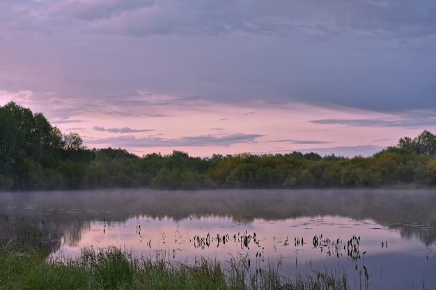 小さな川の上のカラフルで霧のかかった夜明け