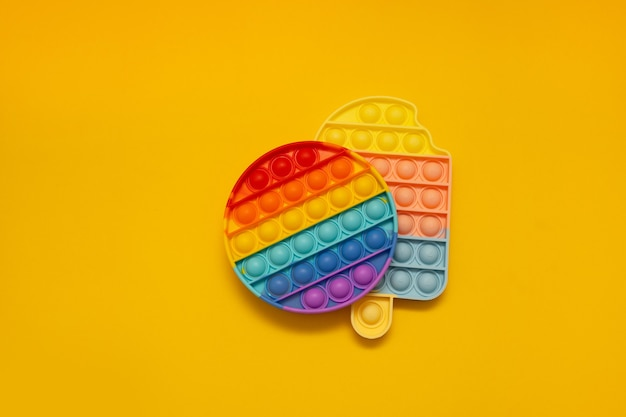 다채로운 안티 스트레스 피젯 푸시는 노란색 배경에 감각 장난감을 팝니다.