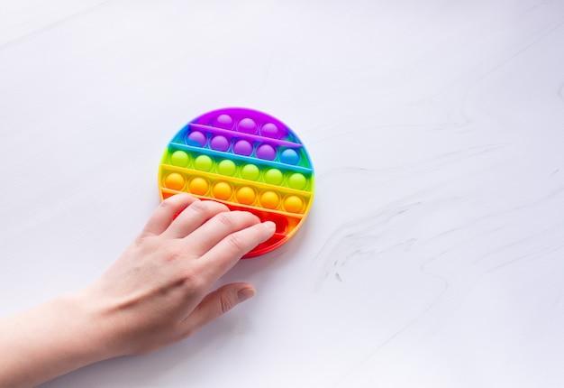 둥근 모양과 손이 있는 다채로운 안티 스트레스 팝 잇 장난감. 손의 미세 운동 기술을 개발합니다.
