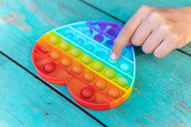 カラフルな抗ストレス感覚おもちゃそわそわプッシュは、子供の手にそれをポップします。女の子はゴム製のおもちゃを指で押してテーブルに置きます。