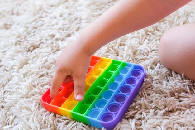 다채로운 스트레스 방지 감각 장난감 피젯 푸시는 아이들의 손에 팝니다. 아이들은 팝 잇 감각 장난감을 가지고 놀고 있습니다. 스트레스와 불안 완화. 스트레스를 받는 어린이와 성인을 위한 트렌디한 실리콘 손놀림 게임