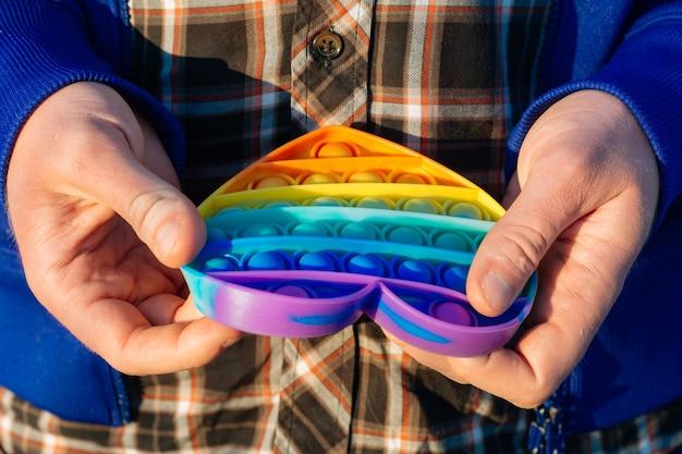 カラフルな抗ストレス感覚おもちゃフィジェットプッシュは、男の手でそれをポップします。男はポップイットおもちゃでストレスを和らげる