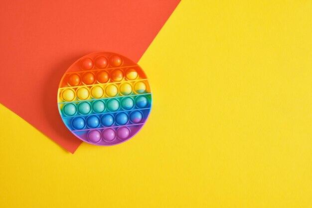 다채로운 스트레스 방지 감각 장난감 피젯 푸시는 빨간색과 노란색 배경 복사 공간 위쪽 보기에 팝니다.
