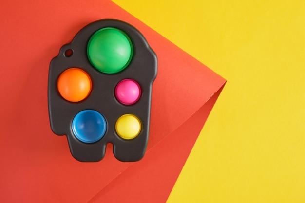 노란색 및 빨간색 배경 복사 공간 상단 보기에 다채로운 스트레스 방지 감각 장난감 피젯 푸시 또는 간단한 보조개