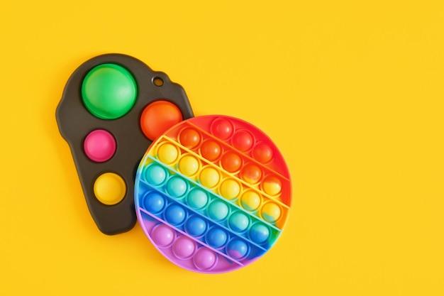 다채로운 스트레스 방지 감각 장난감 피젯 푸시 팝 및 노란색 배경에 간단한 보조개